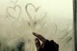 woman drawing heart on wet window