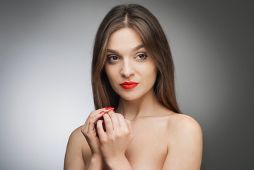 Young beautiful woman with red lips on the gray background