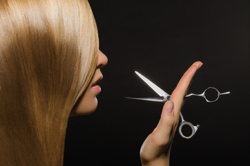 Beautiful woman with straight hair and scissors