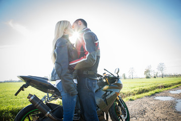 Couple of lovers kissing with motorbike in the background