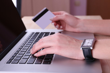 Concept for Internet shopping: hands with laptop and credit
