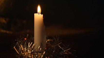 Big burning candle and Christmas decorations aga