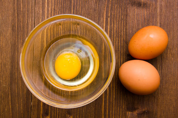 Open egg on bowl on wooden table seen from above