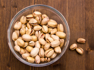 Pistachios on glass bowl on wooden table seen from above