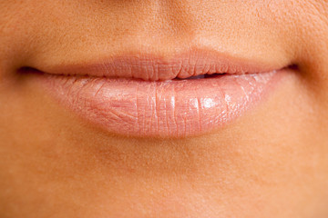 Female lips with applied pink lipstick