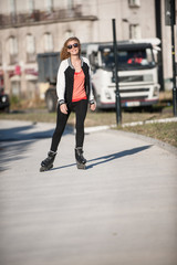 young woman practicing rollerblading in town