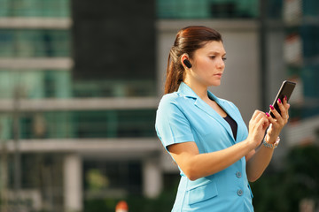 Business woman making a phone call with bluetooth device