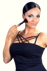 Beautiful smiling black hair girl applying makeup with brush.