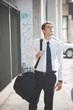 young handsome elegant blonde model man walking with sport bag
