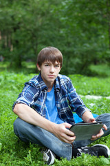 Happy teenager sitting on grass in park