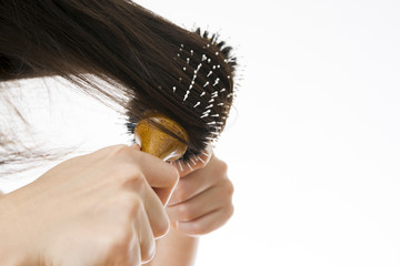Comb in a female hand on a white background