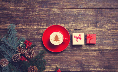 Cup of coffee with cream christmas tree and gift on a table.