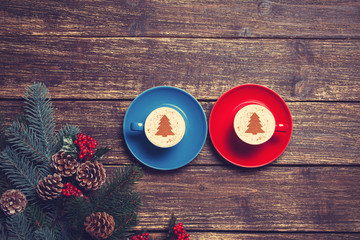 Two cups with christmas tree shape near branch on a wooden table