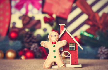 Toy house and gingerbread with christmas gifts on background
