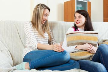 smiling women gossiping on sofa