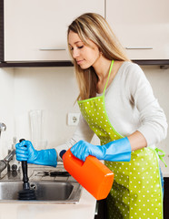 Young housewife cleaning pipe in kitchen