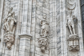 Grungy monuments at facade of Duomo cathedral