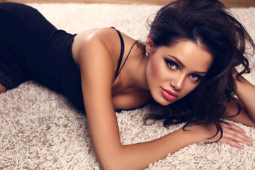 girl with dark hair in lace black dress lying on beige carpet