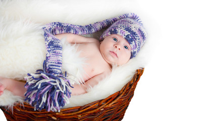 Newborn baby lies in basket in a multi color hat on white backgr
