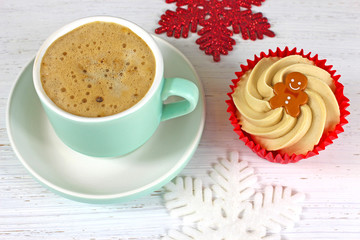 Holiday Coffee and cupcake on a rustic white wood background.