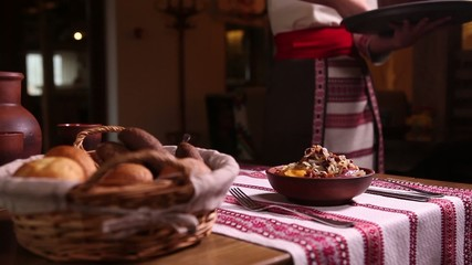 waiter puts on the table dishes - vareniki and borscht