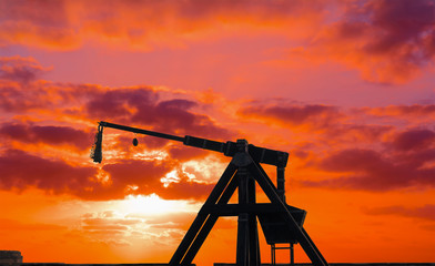 catapult silhouette under a red sunset
