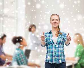 smiling girl showing thumbs up at school classroom