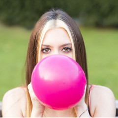 Closeup portrait of beautiful girl inflating balloon, outdoor.