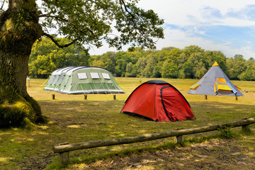 Three big colorful tents in woodlands campground