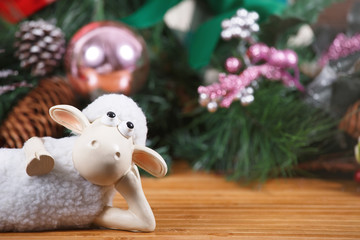 Toy sheep lies at new year background, close up