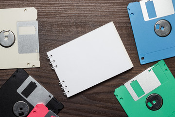 diskettes and blank notebook on wooden background