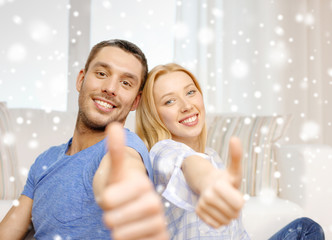happy couple showing thumbs up and hugging