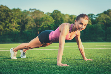 Young woman practicing or exercising. Woman doing push ups