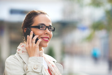 Beautiful young woman with glasses talking on the phone