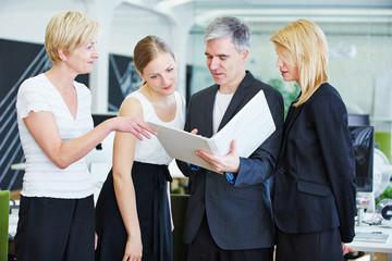 Team im Büro bei Planung mit Akten