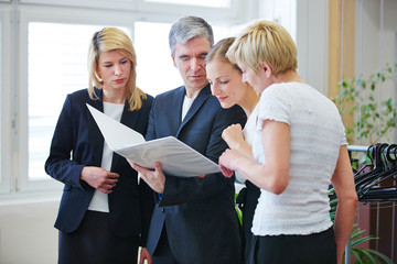 Team schaut gemeinsam in Akte im Büro