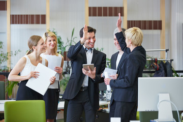 Business Team gibt High Five im Büro