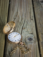 Antique pocket watch  and fob chain on aged wooden boards