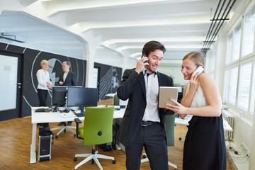 Frau und Mann telefonieren im Büro