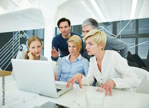 Team im Büro schaut auf Bildschirm von Laptop - 73804161