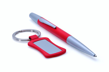 Silver-red metal pen and keychain isolated on white