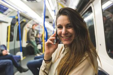 Beautiful Young Woman Using Smart Phone in London Tube