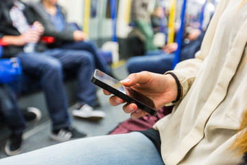 Young Woman Using Smart Phone in London Tube