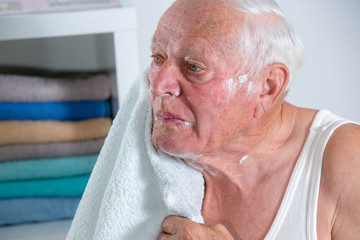 Senior man drying his face with towel after shaving.