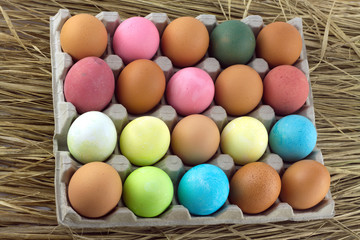 Painted Easter eggs lie in rows inside cells on a straw