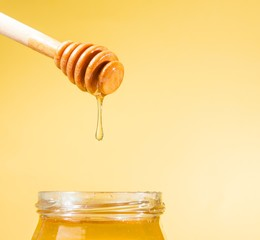 honey jar on golden background with wooden dipper on top