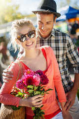 a young couple walking on a market on a sunny morning