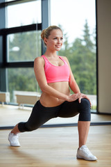 smiling woman stretching leg in gym