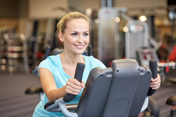 smiling woman exercising on exercise bike in gym
