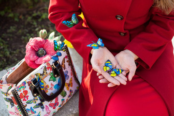 girl in a red coat to hold in hands butterflies